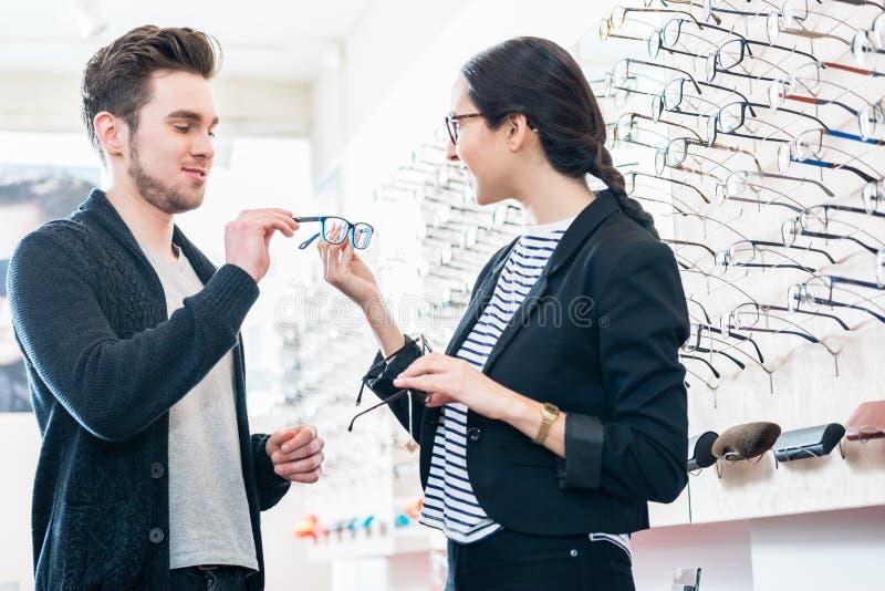 妇女和人买的玻璃在眼镜师商店 免版税图库摄影