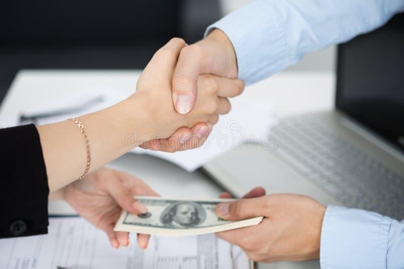 妇女和人握手关闭与在另一韩的金钱 库存图片