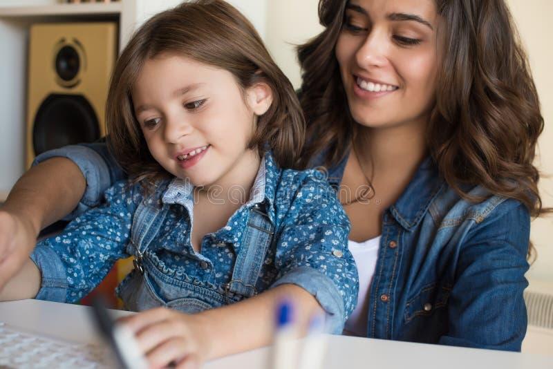 妇女和使用计算机的小女孩 免版税库存图片