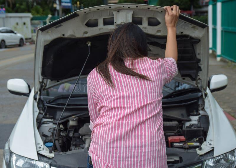 妇女和失败的汽车在检查问题在引擎的路 事故和故障与自动概念 库存图片