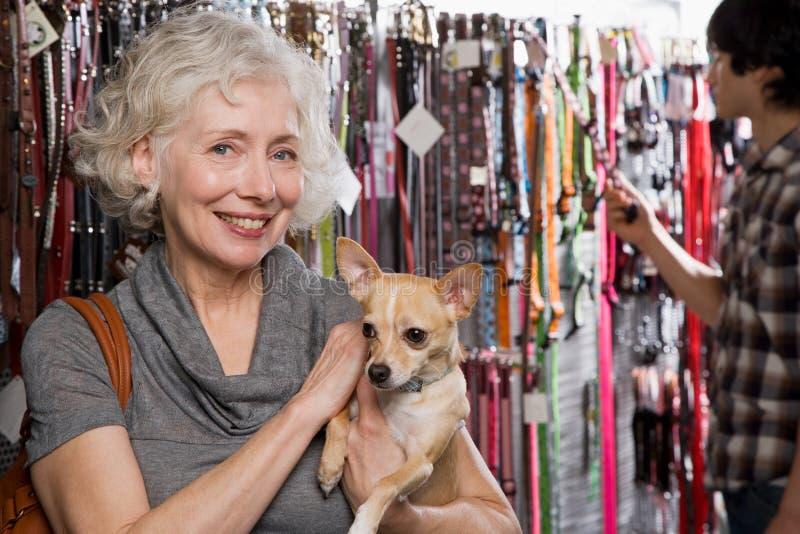妇女和奇瓦瓦狗在宠物店 免版税库存照片