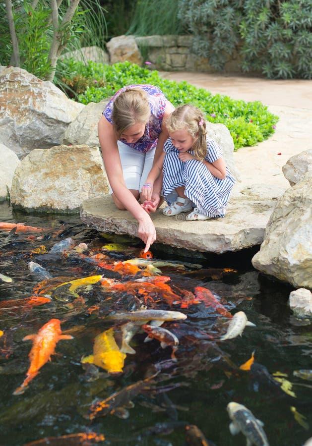 妇女和女儿哺养的鱼 图库摄影