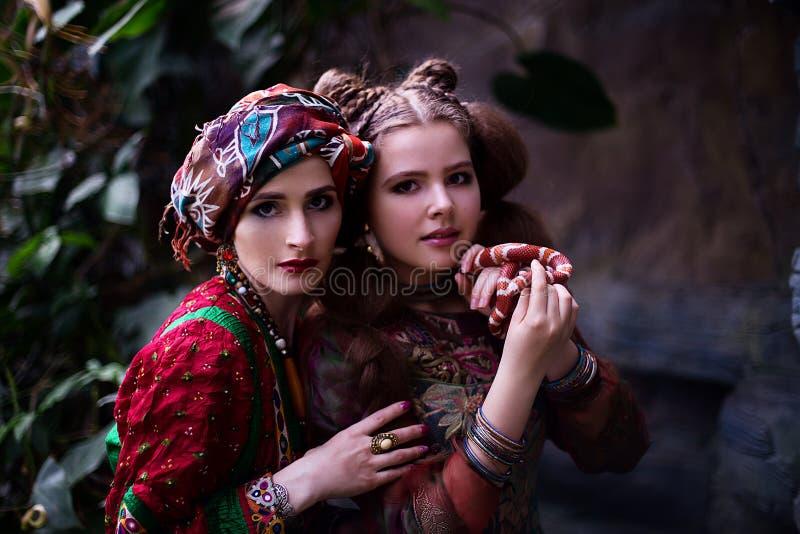 妇女和女孩画象种族衣裳的在热带庭院里 免版税库存照片