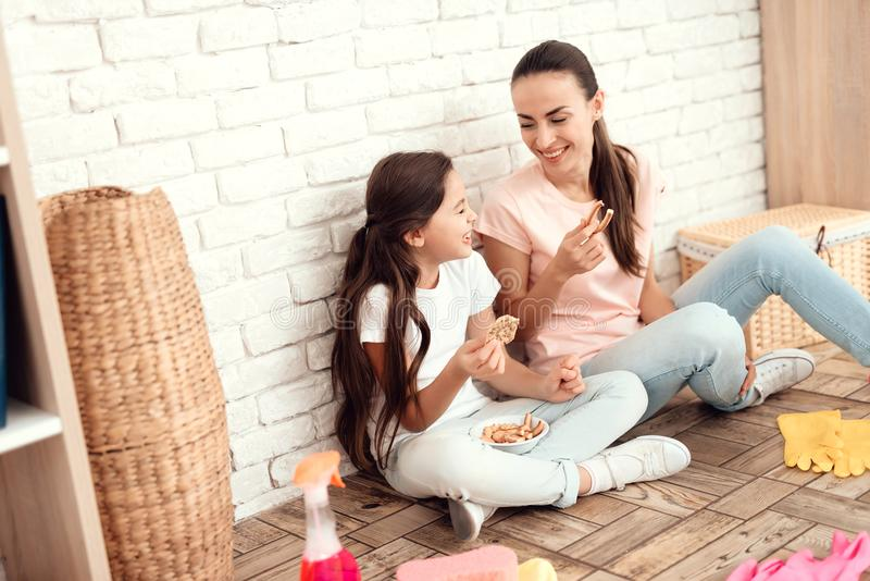 妇女和她的女儿在疲倦房子以后休息 他们坐与他们的后面的地板对墙壁和休息 免版税库存照片
