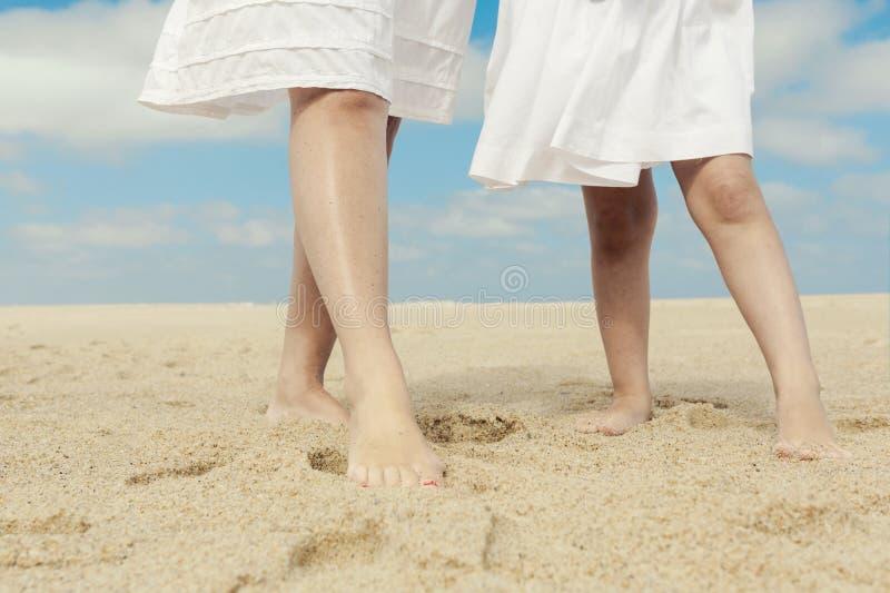 妇女和她的女儿海滩的 免版税库存图片