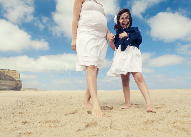 妇女和她的女儿海滩的 免版税库存照片