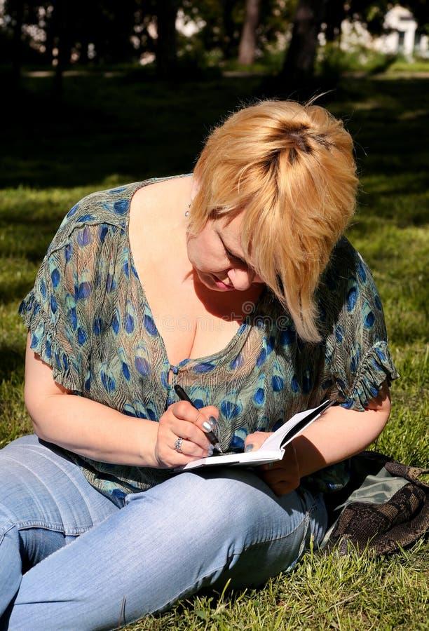 妇女和学生坐草,采取在笔记本的笔记,学会并且写想法,写书 库存照片