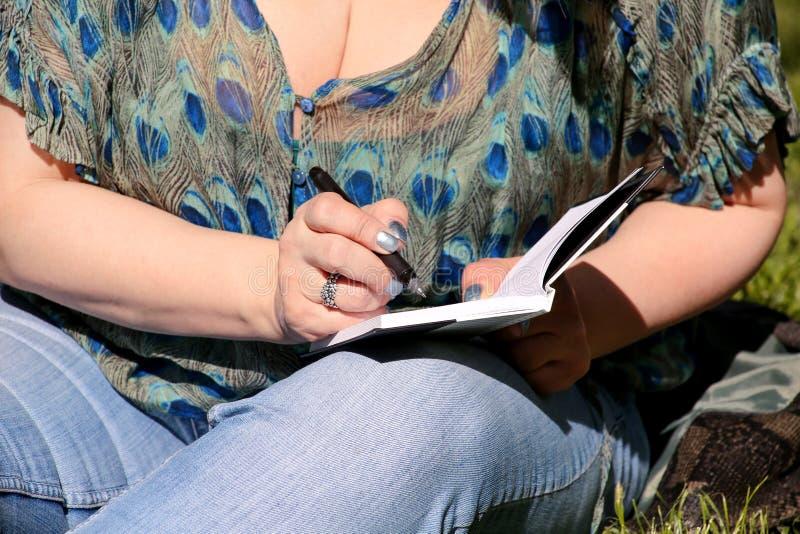 妇女和学生坐草,采取在笔记本的笔记,学会并且写想法,写书 免版税库存图片