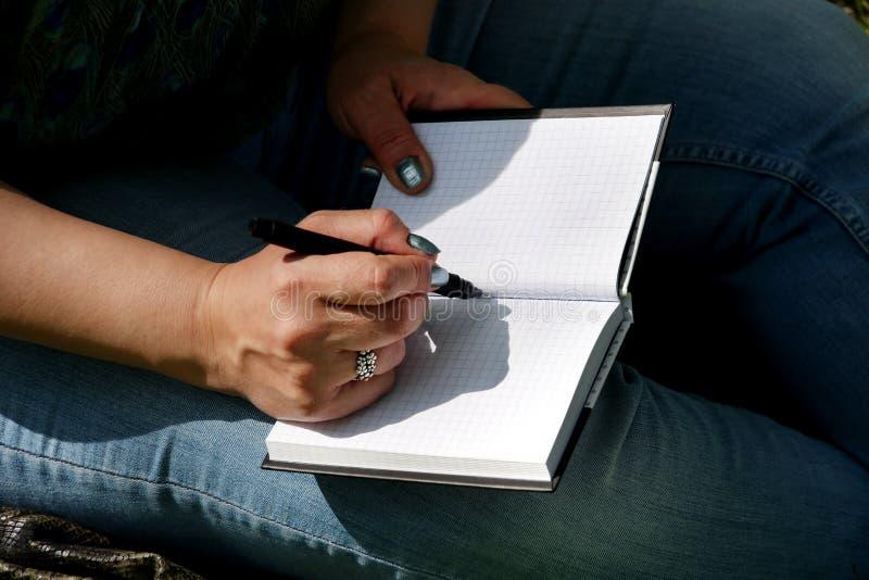 妇女和学生坐草,采取在笔记本的笔记,学会并且写想法,写书 免版税库存照片