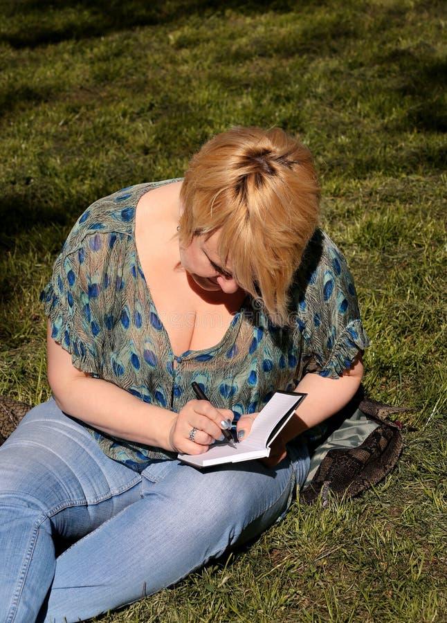 妇女和学生坐草,采取在笔记本的笔记,学会并且写想法,写书 免版税图库摄影