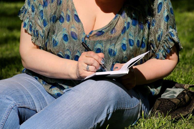 妇女和学生坐草,采取在笔记本的笔记,学会并且写想法,写书 库存图片