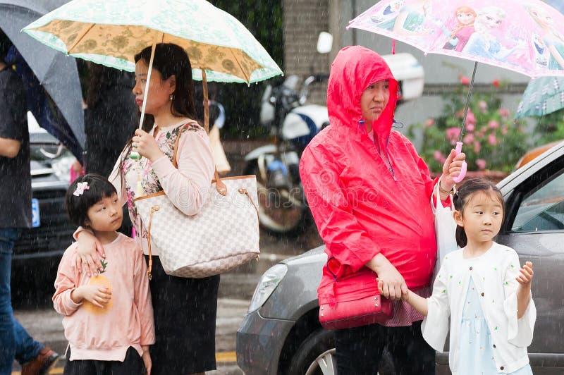 妇女和孩子在雨中的等待一辆公共汽车 免版税库存图片