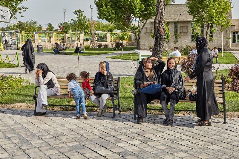 妇女和孩子基于长凳在公园,德黑兰,伊朗 免版税库存图片