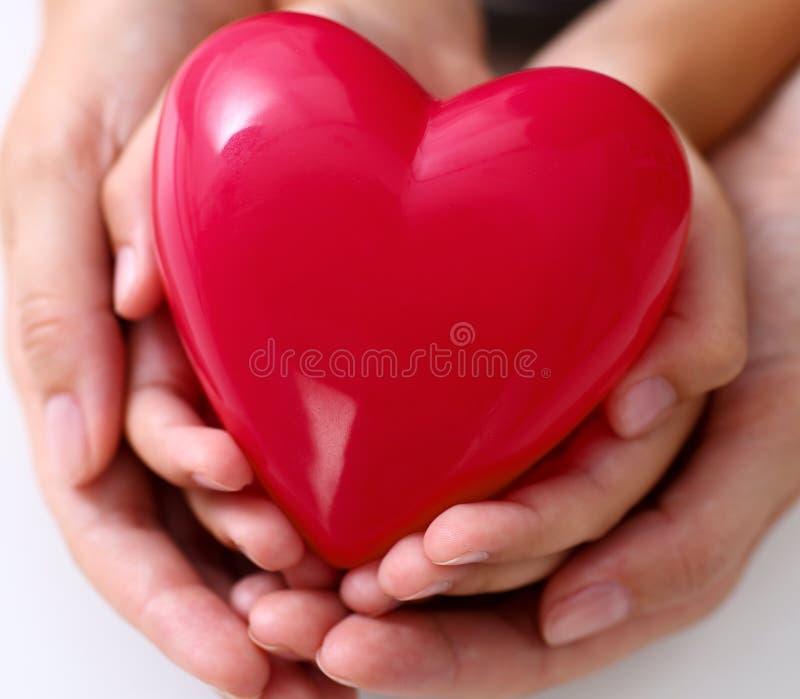 妇女和孩子拿着在胳膊的红色玩具心脏 免版税图库摄影