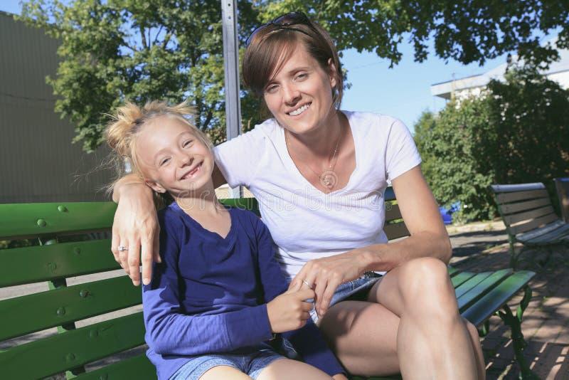 妇女和小女孩坐长凳 免版税库存照片
