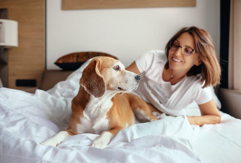 妇女和小猎犬狗在床上叫醒并且见面新的天 免版税库存图片