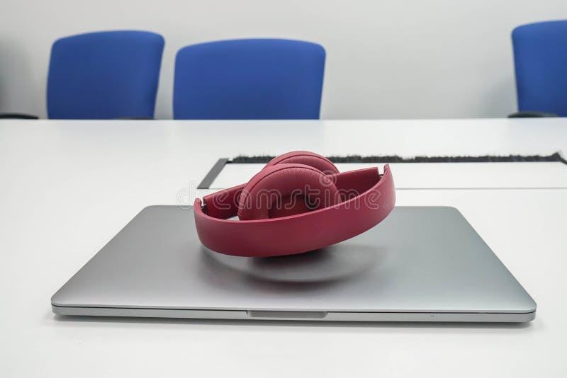 妇女和手提电脑的逗人喜爱的可折叠的无线耳机在工作场所 库存照片