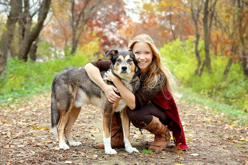 妇女和狗在森林在秋天 库存图片