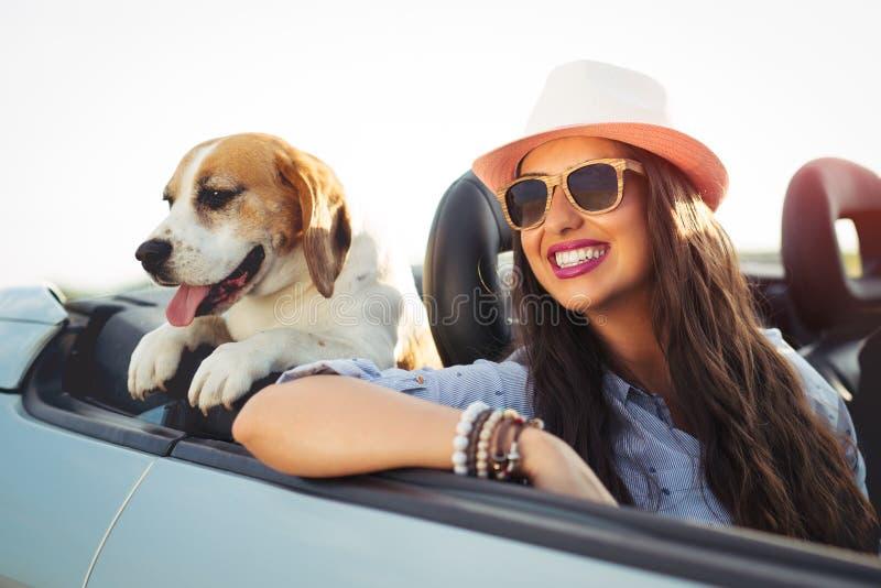妇女和狗在汽车在夏天旅行 免版税库存图片