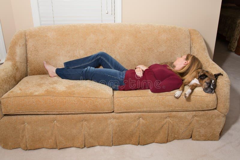 妇女和狗睡着在长沙发- Naptime 库存照片