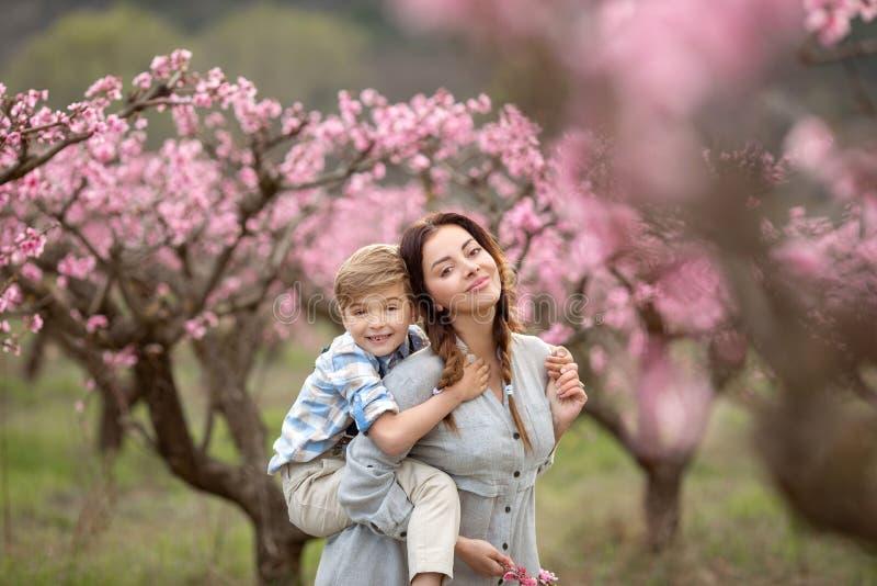 妇女和男孩支持丁香开花的灌木  她嗅到花 r 图库摄影