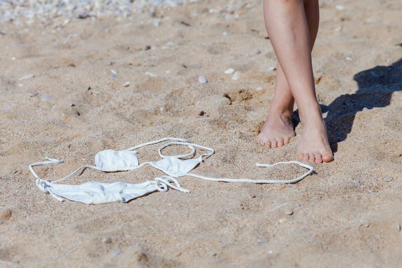 妇女和白色比基尼泳装的被晒黑的脚在沙子 免版税图库摄影