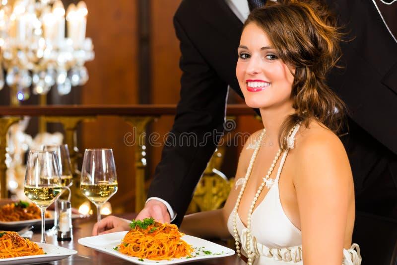 妇女和等候人员在细致的用餐的餐馆 库存图片