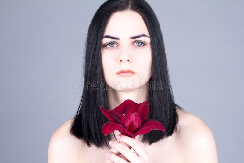 妇女和红色花的光滑的面孔 库存照片