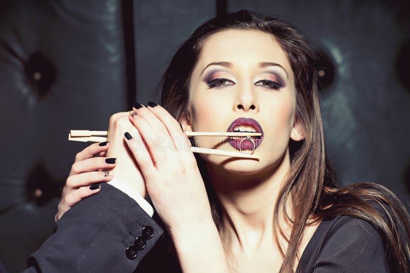 妇女和结婚戒指在筷子 肉欲的妇女举行男性手 有魅力神色的女孩 时装模特儿与 库存图片