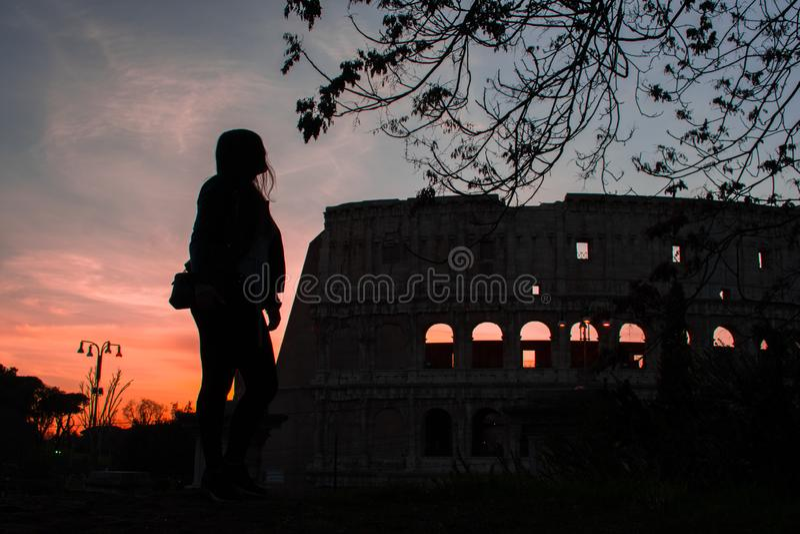 妇女和罗马斗兽场剪影反对五颜六色的日落天空的在罗马意大利 免版税库存照片