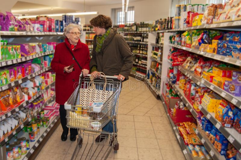 妇女和资深妇女向购物求助在超级市场 免版税库存照片
