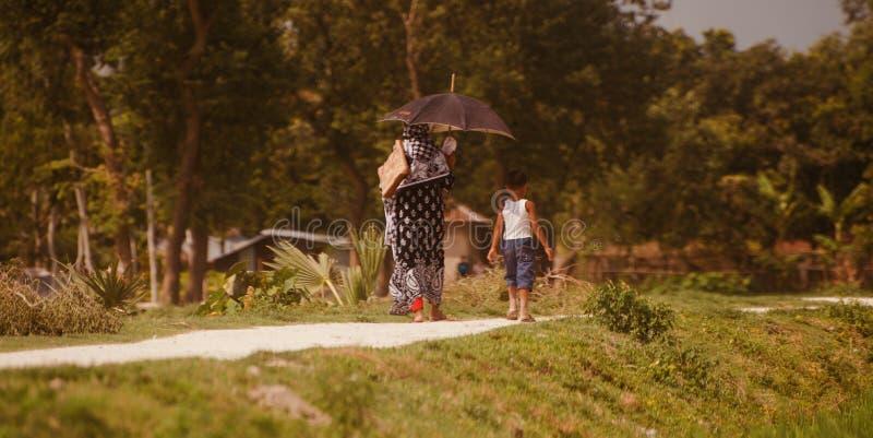 妇女和走在村庄路独特的照片的孩子 库存照片