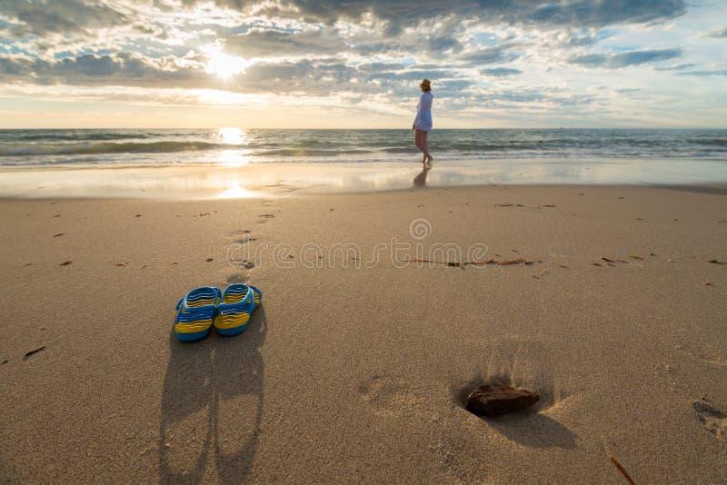 妇女和鞋子在海滩 免版税图库摄影