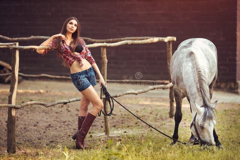 妇女和马 偶然性感的样式 免版税库存图片