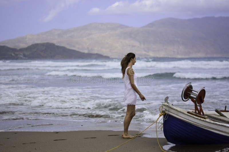 妇女哀伤在小船渔夫、一天风和风大浪急的海面附近 免版税图库摄影
