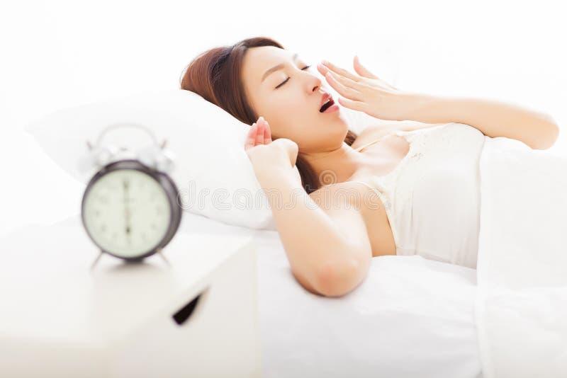 妇女哈欠和睡着在床上 免版税库存图片