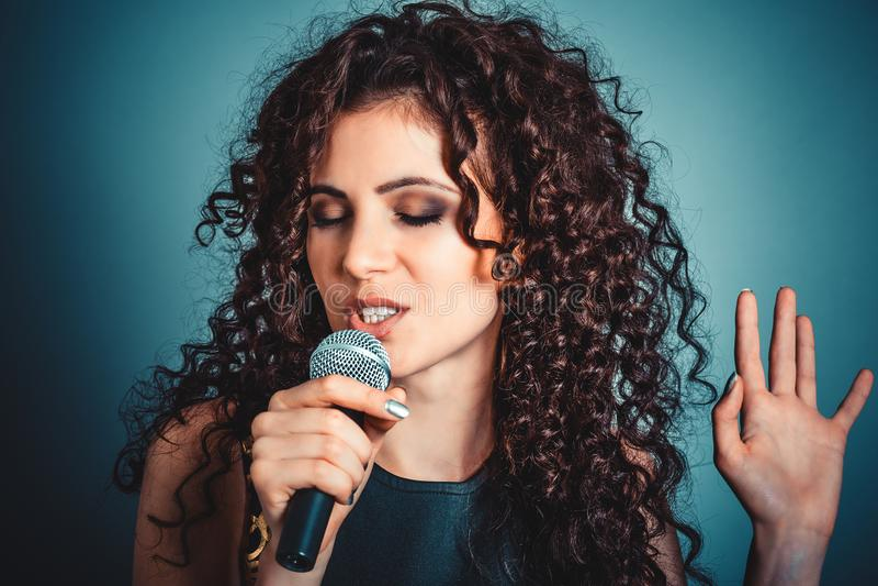 妇女唱歌与眼睛的夫人女孩闭上在卡拉OK演唱 免版税库存照片