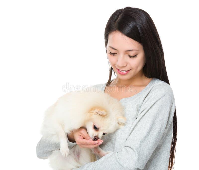 妇女喂养她的狗 免版税库存照片