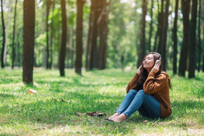 妇女喜欢听到与耳机的音乐充满在公园愉快和放松的感觉 库存照片