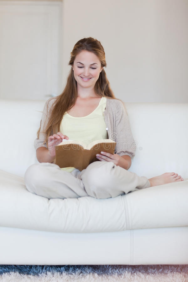 妇女喜欢读书在她的沙发 图库摄影