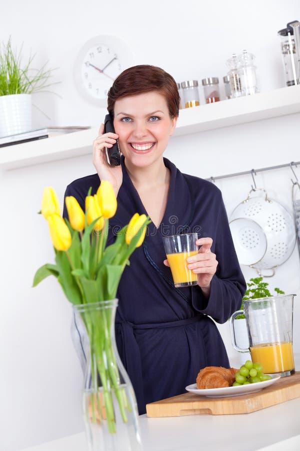妇女喝一杯橙汁和谈话在电话 图库摄影