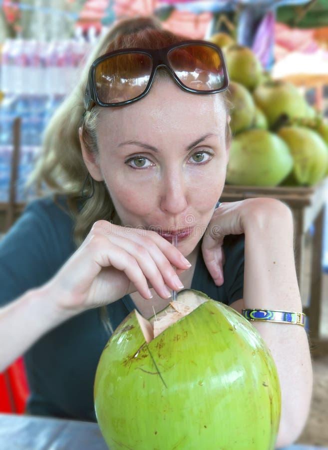 妇女喝从一棵大绿色椰树的椰奶 免版税图库摄影