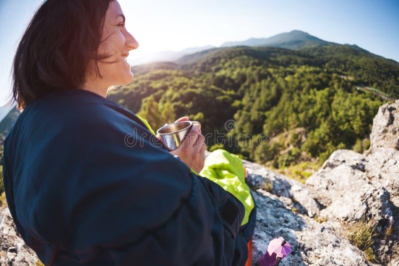 妇女喝咖啡,当坐在山顶部时 睡袋的一个女孩喝从杯子的一份热的饮料 微笑 免版税图库摄影