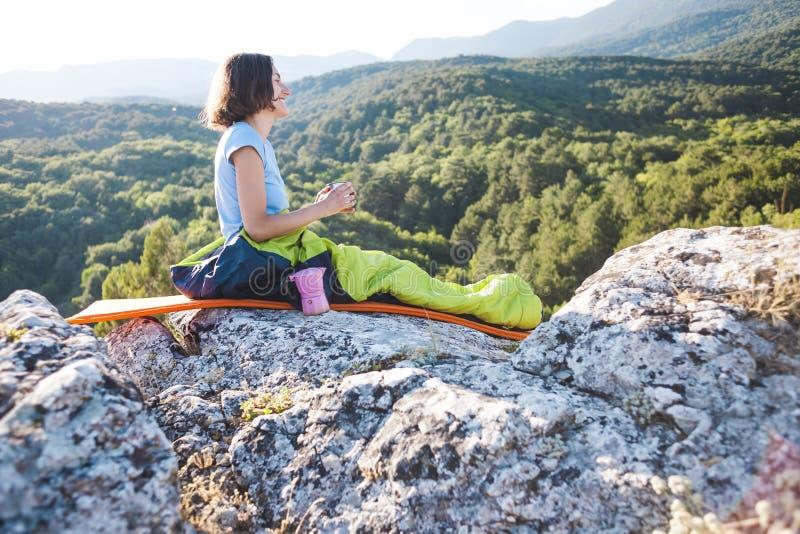 妇女喝咖啡,当坐在山顶部时 睡袋的一个女孩喝从杯子的一份热的饮料 微笑 免版税库存照片