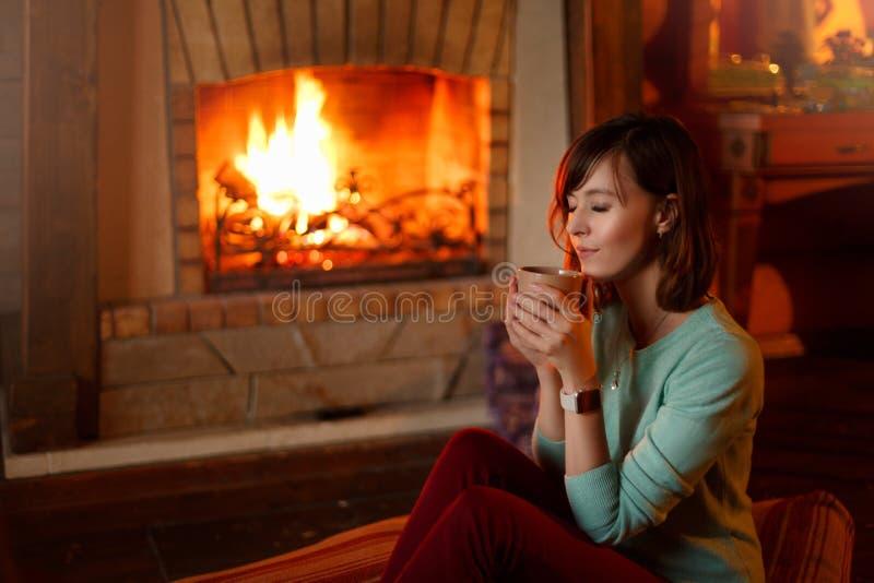 妇女喝茶并且由壁炉温暖自己 年轻白种人女性在家拿着咖啡 温暖 库存照片
