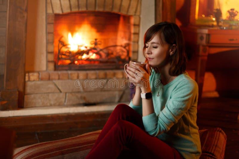 妇女喝茶并且由壁炉温暖自己 年轻白种人女性在家拿着咖啡 温暖 免版税图库摄影