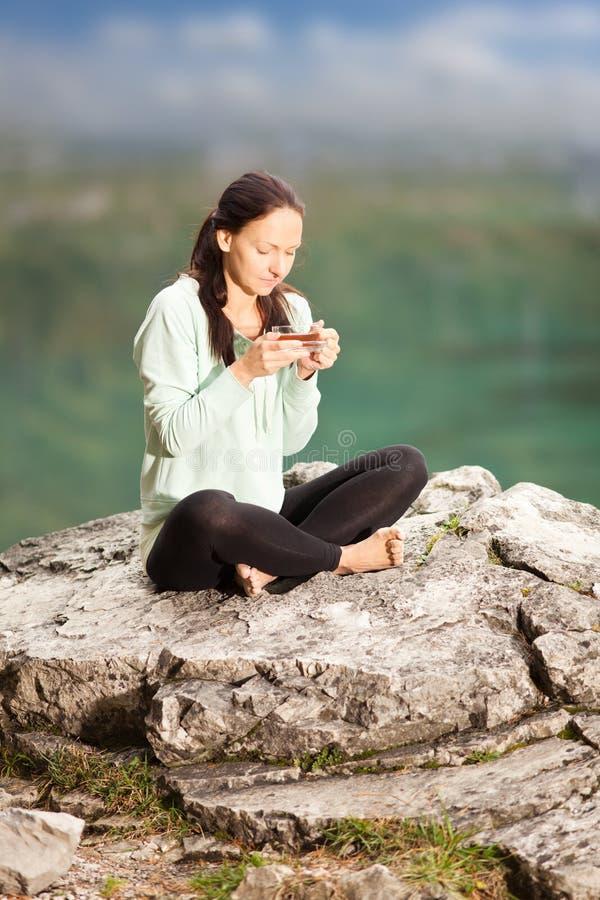 妇女喝茶本质上 免版税库存图片