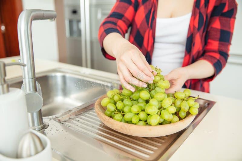 妇女在一个木碗投入绿色葡萄 免版税图库摄影