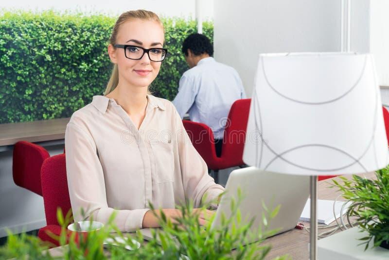 妇女在一个热的书桌办公室 免版税库存图片