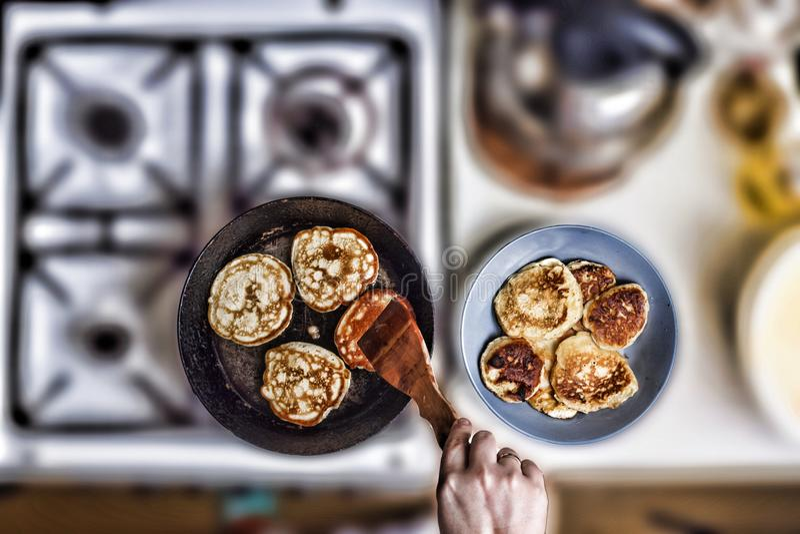 妇女在一个煎锅的油炸物薄煎饼在老煤气炉 概念:烹调,烘烤 在视图之上 文本的空位 免版税库存照片